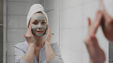 Adult woman with a towel on her head applying clay mask on her face looking at Live Action