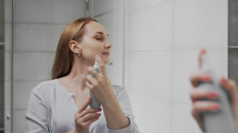 Adult woman applying water spray for skin hydration Live Action
