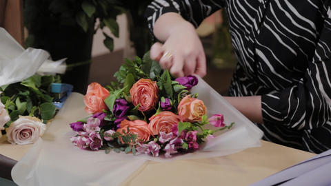 Professional florist is packing a bouquet. Beautiful bouquet for International Live Action