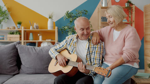Retired couple playing the guitar and singing enjoying romantic day indoors at Live Action