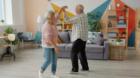 Slow motion of cheerful elderly people dancing at home smiling laughing having Live Action