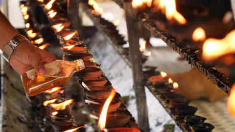 Closeup 4k video of worshipper pouring sacred oil in burning lamp at altar of Live Action