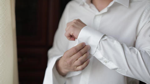 Handsome groom man fixes his cuffs on a jacket with cufflinks. Businessman Live Action