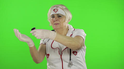 Elderly female doctor pours pills into her hand. Female nurse. Virus protection Live Action