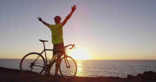 Cycling success and achievement - man cheering reaching goal happy on road bike Live Action