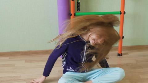 Cheerful girl teenager dancing sitting on floor in school gym. Happy girl Live Action
