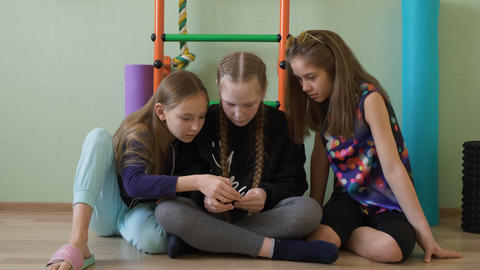 Three school girl using mobile phone in gym class at break. Teenager girl Live Action