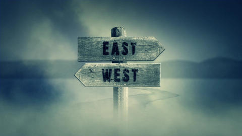 Old Wooden Sign on a Middle of a Cross Road With the Words East or West Footage