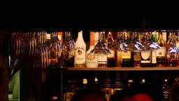 4K Ungraded: Bottles of Liquor on Shelf of Bar With Customers Footage