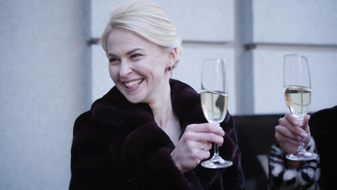 Portrait of positive gorgeous Caucasian blond woman drinking champagne with Live Action