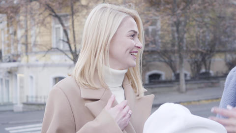 Close-up of cheerful blond Caucasian girl chatting with friends outdoors. Young Live Action