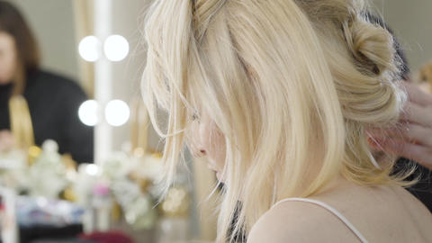 Close-up of hairdress of blond young woman sitting in beauty salon. Beautiful Live Action