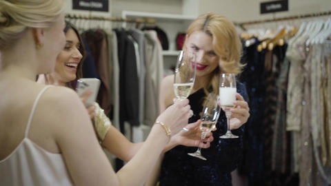 Three positive Caucasian women clinking glasses with champagne in fashion Live Action