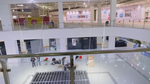 men assemble illuminating construction in shopping center Live Action