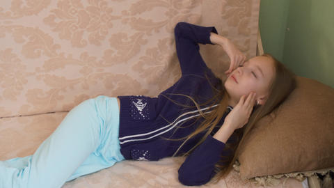 Sleeping teenager girl waking up on soft couch in cozy home. Awakened girl Live Action