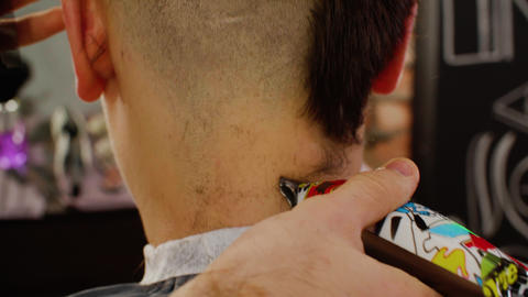 Barber shaving long hair to bald with electrical shaver. Man shaving hair with Live Action