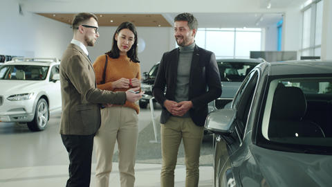 Friendly professional car dealer discussing new auto with cheerful clients man Live Action