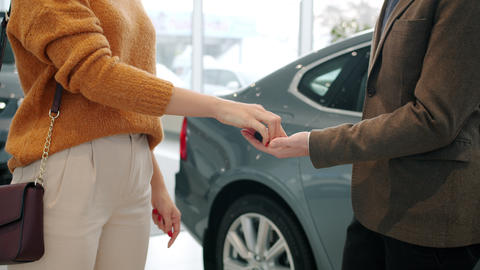 Woman getting car keys from salesman then shaking hands to celebrate successful Live Action