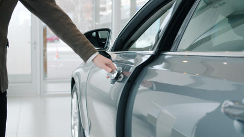 Close-up shot of male hand opening car door in luxury auto dealership looking Live Action