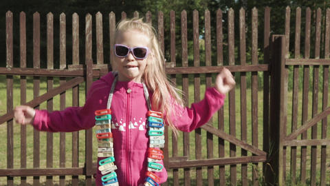 Country child girl in sunglasses dancing with necklace of clothes pegs Live Action