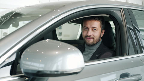 Portrait of bearded guy new car owner sitting inside beautiful automobile Live Action