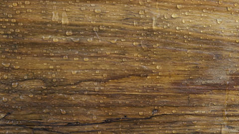 Slow motion. Drops of rain fall on a wooden surface and flow down drops on a Live Action