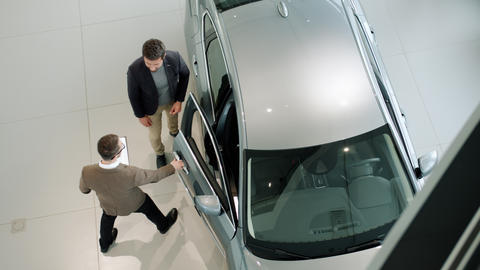 Young businessman talking to car dealer then sitting in automobile in dealership Live Action
