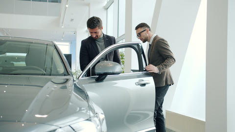Salesman opening car door for buyer selling new automobile in dealership Live Action