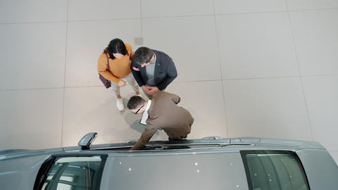 Top view of young family choosing car in showroom discussing automobile with Live Action