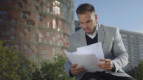 Businessman looking at papers on street. Manager celebrating success outside Live Action