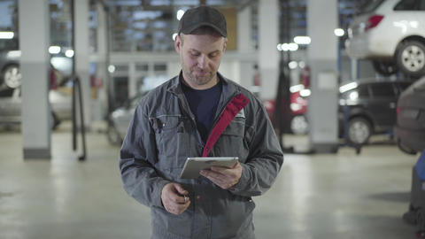 Camera approaching to male auto mechanic holding tablet and showing car keys at Live Action