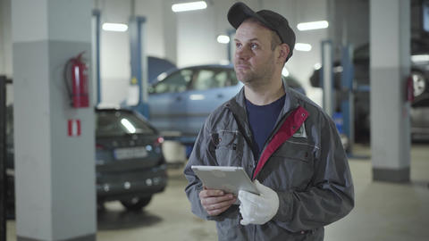 Adult professional Caucasian auto mechanic looking around in repair shop Live Action