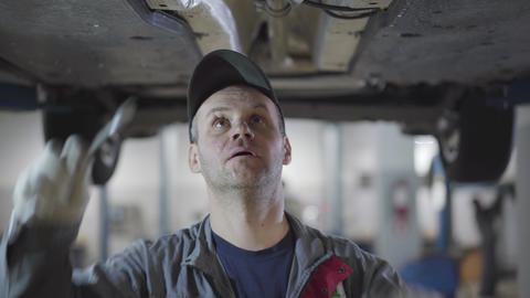 Close-up portrait of professional auto mechanic tightening screws with Live Action