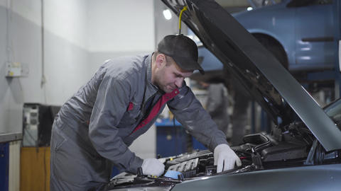 Portrait of adult Caucasian man in workwear examining open car hood manually and Live Action