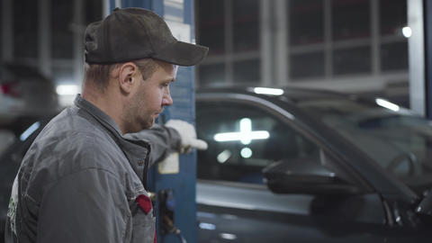 Side view portrait of professional Caucasian auto mechanic raising up car with Live Action
