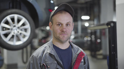 Close-up portrait of adult Caucasian man workwear standing in auto repair shop Live Action