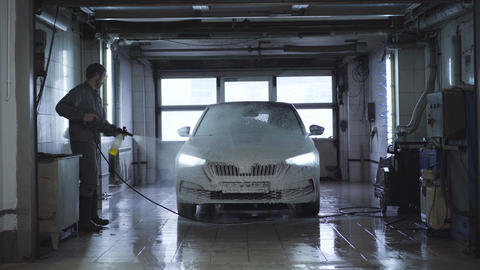 Wide shot of worker washing vehicle in car wash. Caucasian employee using high Live Action