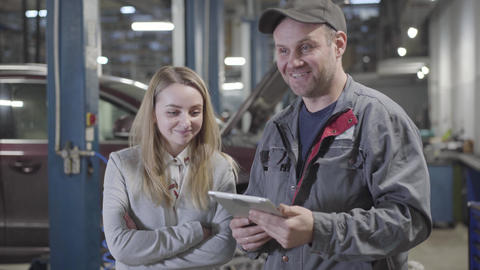 Portrait of adult Caucasian man and woman discussing automobile repair at Live Action