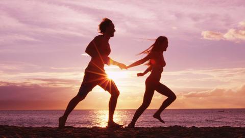 Beach couple running having fun holding hands on beach enjoying romantic sunset Live Action