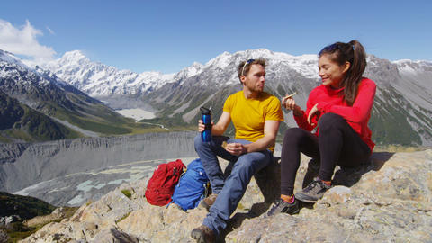 Hiking people taking food break on alpine hike in New Zealand by Mount Cook Live Action