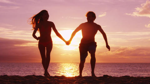 Romantic sunset beach couple holding hands on beach running having fun on travel Live Action