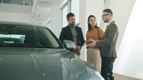 Cheerful family buying car in dealership talking to manager looking at new auto Live Action