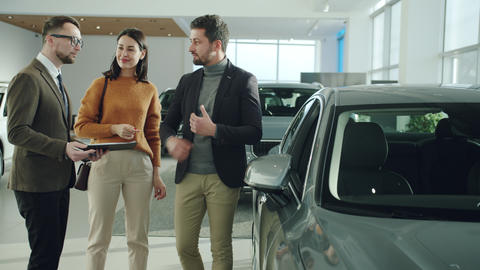 Cheerful husband and wife purchasing vehicle in car dealership talking to Live Action