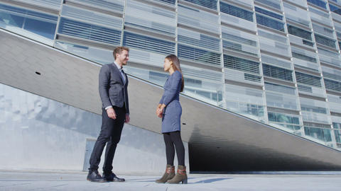 Business people - business man and business woman talking by office building Live Action