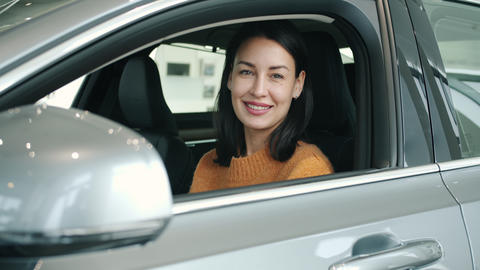 Portrait of girl inside new automobile in car dealership smiling looking at Live Action