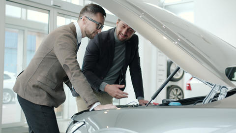 Cheerful men sales manager and client watching car engine under motor hood Live Action