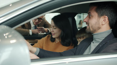 Cheerful people choosing car in showroom talking to manager sitting in Live Action