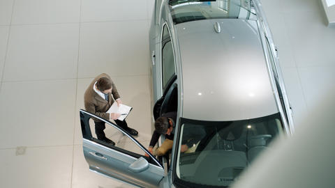 Sales manager opening car door and inviting customer to see the auto inside Live Action