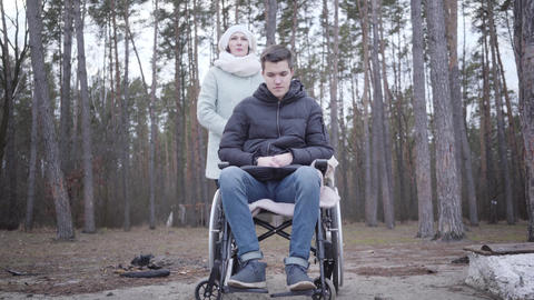 Adult Caucasian woman holding shoulder of sad disabled boy in wheelchair and Live Action
