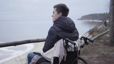 Depressed Caucasian boy in wheelchair spending autumn day alone on river bank Live Action